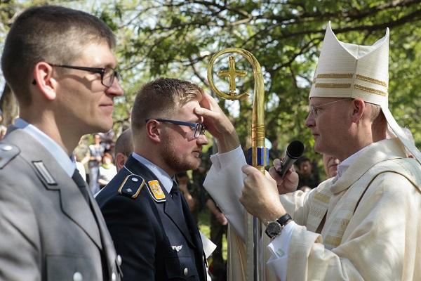Militärbischof Overbeck spendet Leutnant Kevin und Hauptgefreitem Alex das Sakrament der Firmung. © Christina Lux