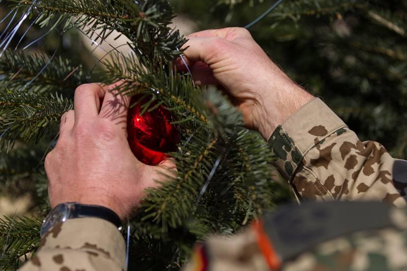Ein Soldat im Einsatz schmückt einen Christbaum © Bundeswehr / Jane Schmidt