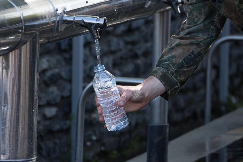 Ein Soldat füllt Wasser aus der Grotte in Lourdes in seine Wasserflasche. © Bundeswehr / Torsten Kraatz