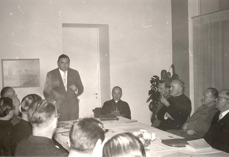 Bundesverteidigungsminister Franz Josef Strauß (stehend) war Gast auf der zweiten Gesamtkonferenz der Katholischen Militärseelsorge im November 1957 in Maria Laach. Sitzend rechts von ihm Militärbischof Joseph Kardinal Wendel. Die Zuhörer dürften fast alle Militärpfarrer sein. Quelle: AKMB